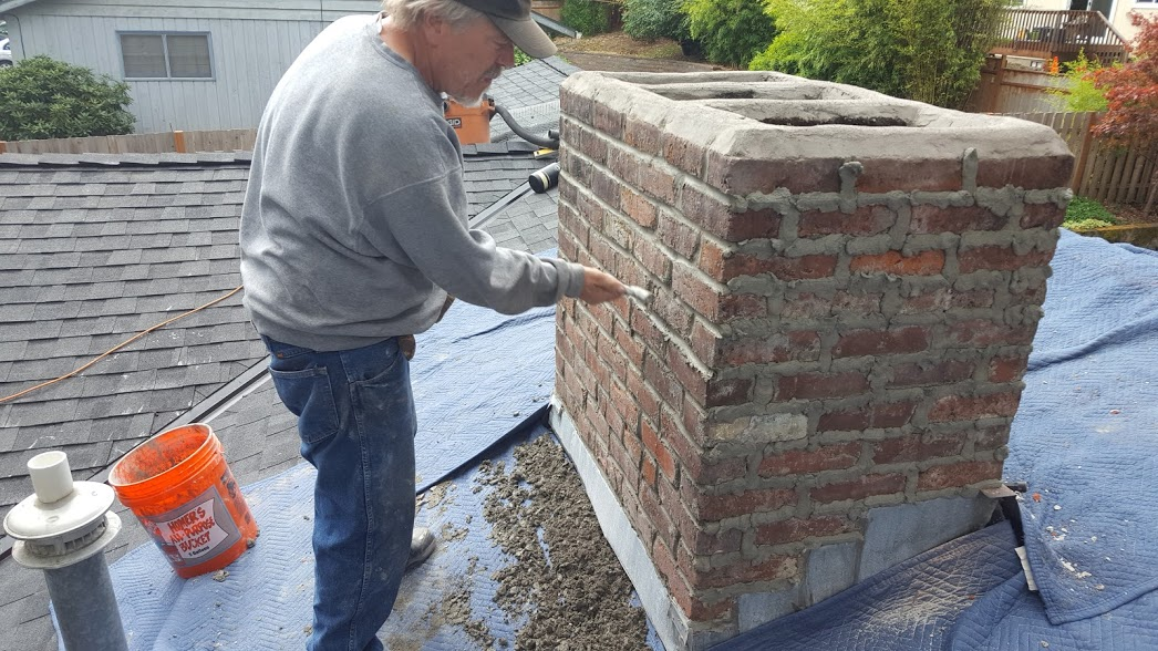 A worker tooling new mortar into prepared chimney mortar joints.