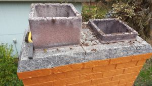 A chimney crown, cracked, still bonded well to the top brick of the chimney.