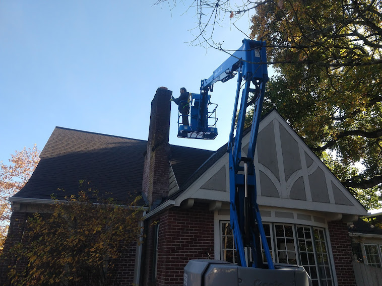 Worker on a mechanical lift, performing repairs on a chimney.