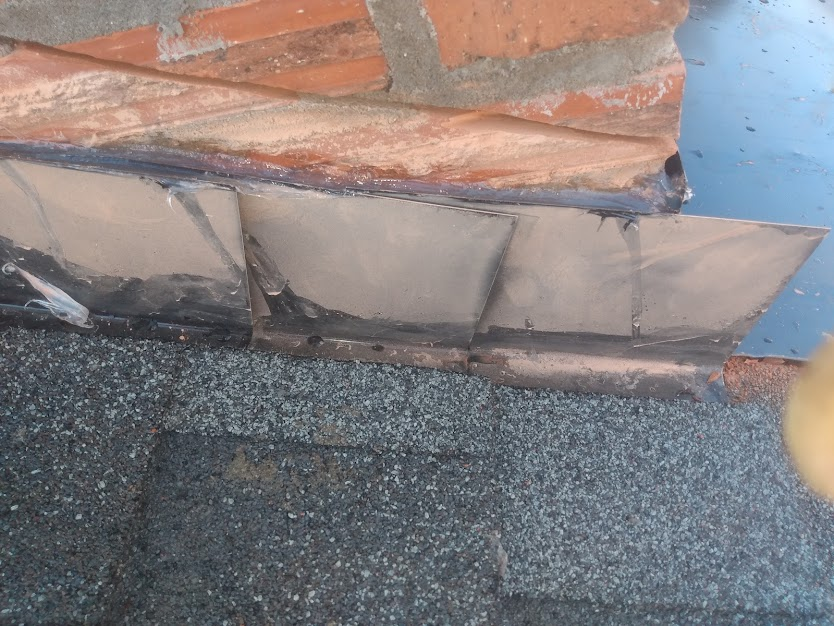 Roof flashing up against a chimney