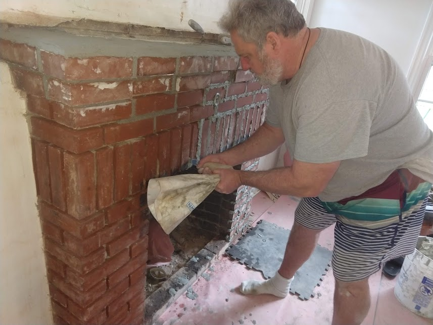 Tuckpointing a brick fireplace mantle.