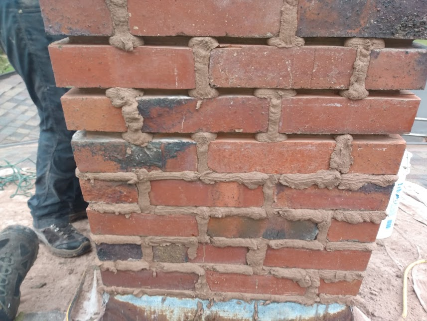 A chimney that has had bad mortar joints ground out with a grinder, then new mortar is being tooled into the prepared joints.