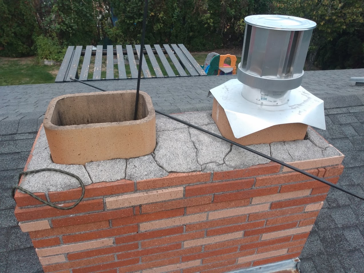 Severely cracked and deteriorated chimney crown. Needs to be replaced with a new crown.